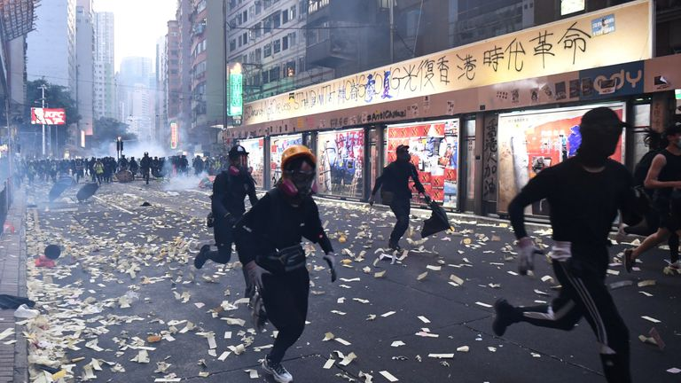 Protesters run from police during clashes in the Wanchai district in Hong Kong on October 1, 2019