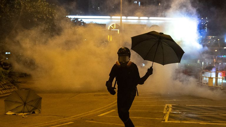 An anti-government protester runs away from a tear gas canister, after leader Carrie Lam announced emergency laws that would include banning face masks at protests