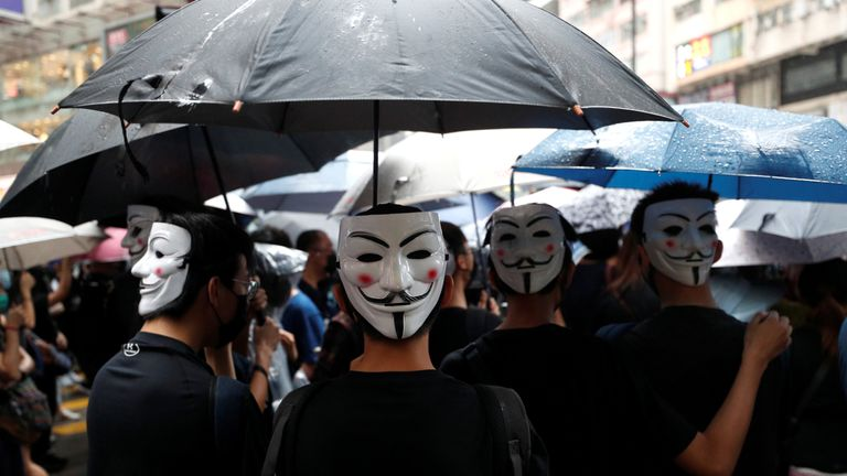 Pro-democracy protesters wearing masks gather in Causeway Bay on Sunday for the latest anti-government rally