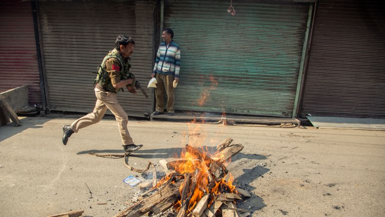 An Indian policeman chases Kashmiri protesters