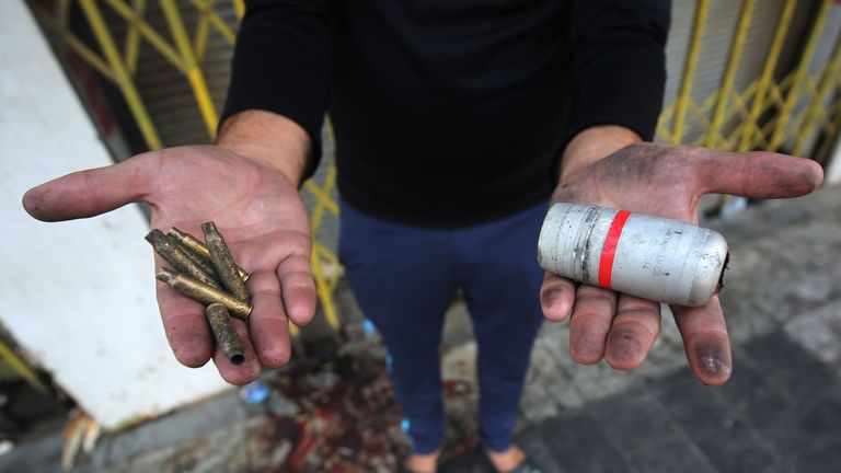 A protester holds the casings of live rounds (L) and a spent tear gas canister (R) reportedly fired by riot police