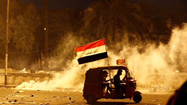 A tuk-tuk drives away from tear gas fired by Iraqi security forces during a protest over corruption, lack of jobs, and poor services, in Baghdad, Iraq October 26, 2019