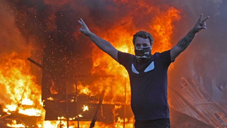 A protester flashes the V for victory sign as a riot police vehicle burns in Baghdad on Thursday