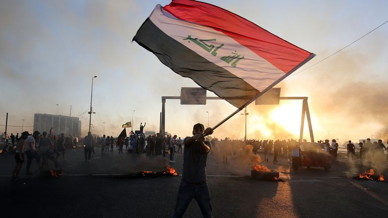 An Iraqi protester waves the national flag during protests on Saturday