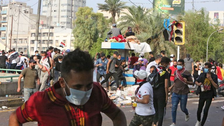 Iraqi protesters run from tear gas in Baghdad