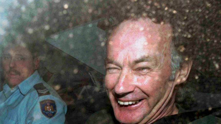 FILE - In this Nov. 4, 1997, file photo, Ivan Milat smiles in a police car after attending a court in Sydney, Australia. Milat, whose grisly serial killings of young backpackers horrified Australians in the early '90s, died in a Sydney prison on Sunday, Oct. 27, 2019, prison authorities said. He was 74. (AP Photo/Rick Rycroft, File)