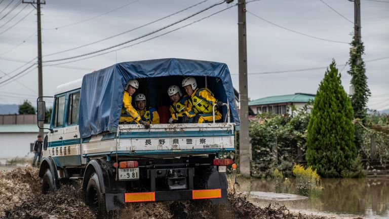 NAGANO, JAPAN - OCTOBER 14: Rescue workers sit in the back of a truck as it drives on a road that was flooded by Typhoon Hagibis, on October 14, 2019 in Nagano, Japan. Japan has mobilised 110,000 rescuer workers after Typhoon Hagibis, the most powerful storm in decades, swept across the country leaving 37 dead and around 20 missing. (Photo by Carl Court/Getty Images)