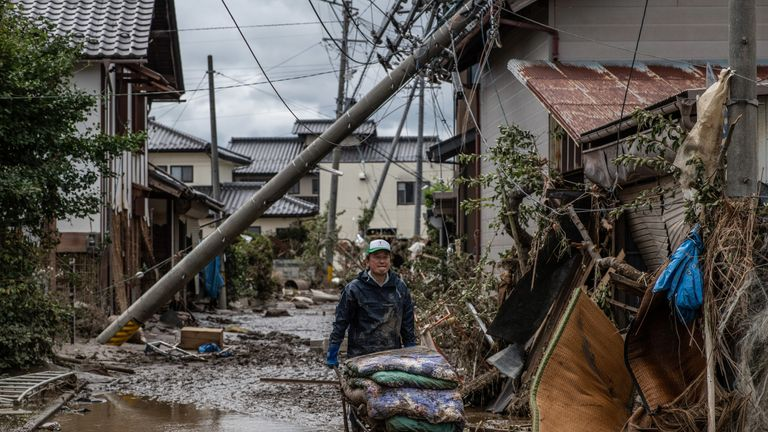 NAGANO, JAPAN - OCTOBER 15: A man pushes a wheelbarrow after clearing belongings from a property that was damaged by heavy flooding caused by Typhoon Hagibis, on October 15, 2019 in Hoyasu near Nagano, Japan. Japan has mobilised over 100,000 rescue workers after Typhoon Hagibis, the most powerful storm in decades, swept across the country killing 66 people and leaving thousands injured and homeless. (Photo by Carl Court/Getty Images)