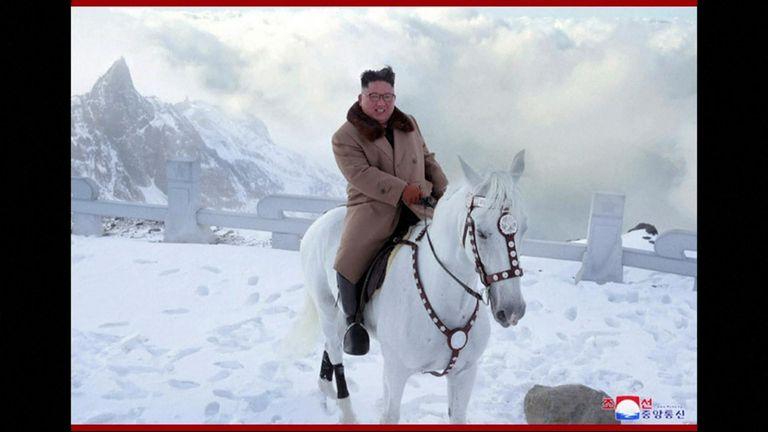 Kim riding a white horse on a sacred mountain