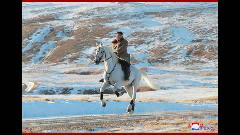 Kim riding a white horse on a sacred mountain