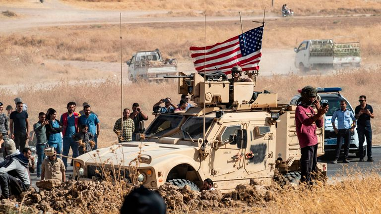 Syrian Kurds gather around a US armoured vehicle during a demonstration against Turkish threats to attack them