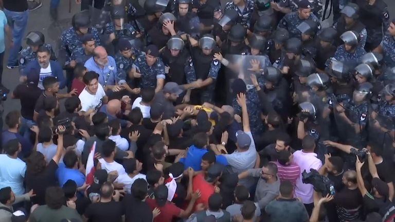 Hezbollah supporters pushed into a peaceful demonstration in Beirut, briefly clashing with protesters and prompting riot police to intervene.