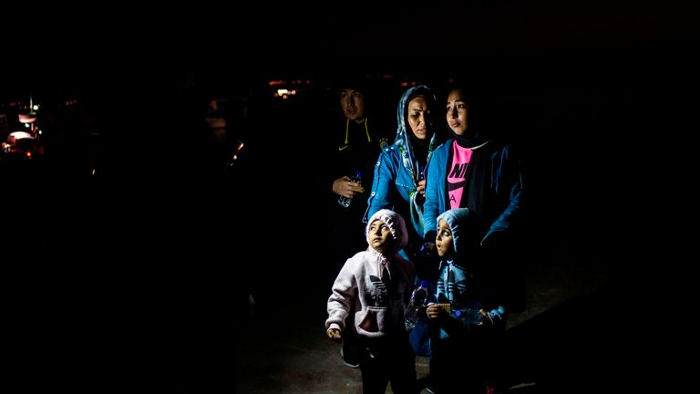 """TOPSHOT - Migrants wait to board in a bus as they transfer to a camp, following a rescue operation by a Frontex patrol vessel, at the port of Skala Sikamias, on the island of Lesbos, on October 2, 2019. - Fisherman Christos Halkiotis in the village of Skala on the Greek island of Lesbos gives short shrift to a promised Greek government crackdown to curb rising migration flows. """"It's all up to the Turks,"""" said Halkiotis, calmly unspooling his lines and hooks in a bucket. """"They're the ones letting"""