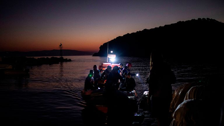 """TOPSHOT - Migrants are seen on board a ''Refugee Rescue NGO'' rescue boat, following a rescue operation by a Frontex patrol vessel, at the port of Skala Sikamias, on the island of Lesbos, on October 2, 2019. - Fisherman Christos Halkiotis in the village of Skala on the Greek island of Lesbos gives short shrift to a promised Greek government crackdown to curb rising migration flows. """"It's all up to the Turks,"""" said Halkiotis, calmly unspooling his lines and hooks in a bucket. """"They're the ones le"""