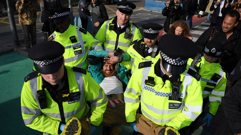 An arrested demonstrator smiles as he is carried away by police