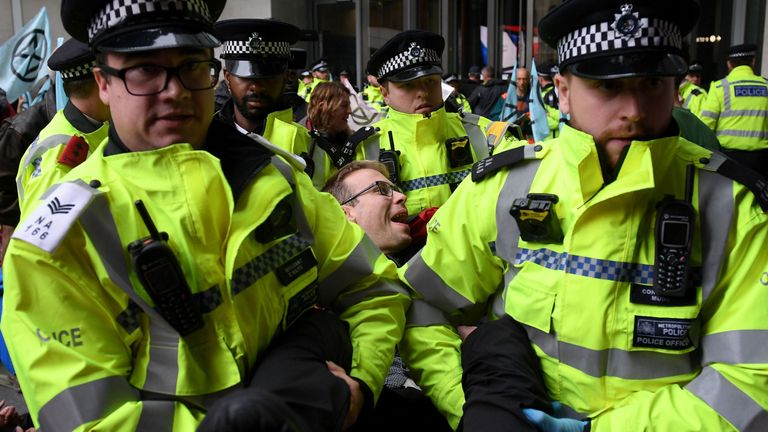 Police carry away an Extinction Rebellion protester outside the BBC's headquarters in London
