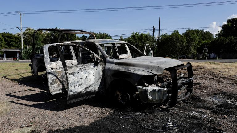 The burnt wreckage of a police patrol car after an ambush by suspected cartel on police officers in El Aguaje, in Michoacan state, Mexico