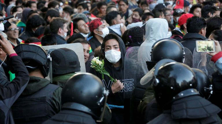 A demonstrator holds flowers while standing in front of police during a protest in La Paz, Bolivia, October 22, 2019