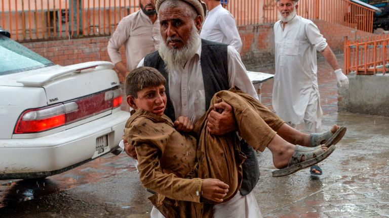 A worshipper carries a young boy after the mosque explosion