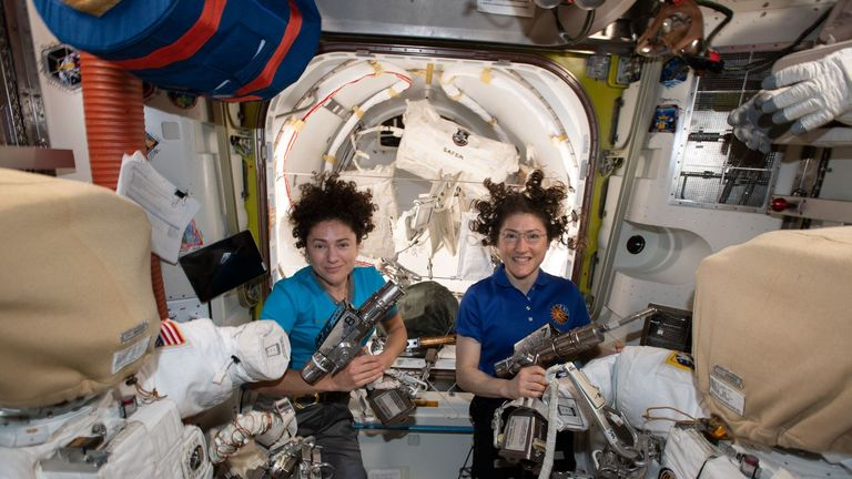NASA astronauts Jessica Meir (left) and Christina Koch (right) prepare spacesuits and tools they will use on their first spacewalk together, 15 October, 2019