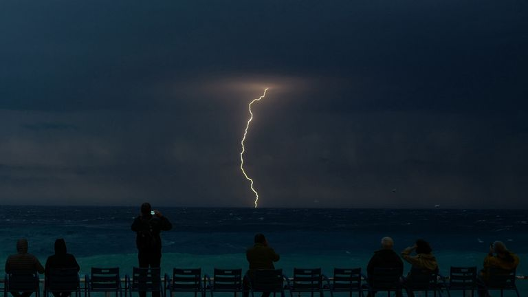 People watching a thunderstorm above the Mediterranean sea on the French Riviera city of Nice