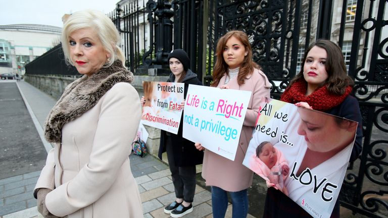 Bernadette 'Bernie' Smyth (L), founder of pro-life campaign group Precious Life, stands with anti-abortion activists holding placards outside, Belfast High court in Belfast, on January 30, 2019, where Northern Ireland resident and campaigner Sarah Ewart, who after having been diagnosed with a fatal foetal abnormality in 2013 travelled to England for a termination, is a bringing a legal challenge against Northern Ireland's restrictive abortion laws. - Britain's Supreme Court, the highest court in
