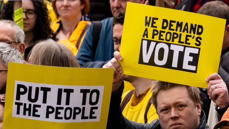 People hold up placards as they attend a march and rally organised by the pro-European People's Vote campaign for a second referendum in central London on March 23, 2019. - Hundreds of thousands of pro-Europeans from across Britain were expected to march through London on Saturday calling for another referendum on EU membership with the country mired in political paralysis over Brexit. (Photo by Niklas HALLE'N / AFP)
