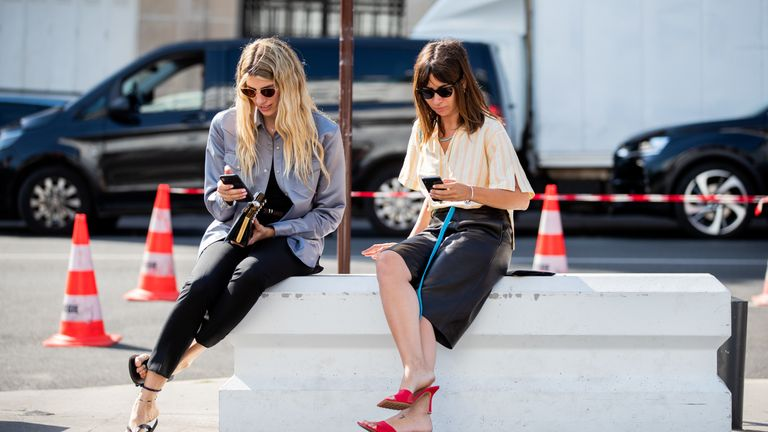 PARIS, FRANCE - JUNE 30: Veronika Heilbrunner is seen wearing grey jacket and Natasha Goldenberg is seen wearing black shorts, yellow stripped button shirt seen typing text message on their phone outside Acne during Paris Fashion Week - Haute Couture Fall/Winter 2019/2020 on June 30, 2019 in Paris, France. (Photo by Christian Vierig/Getty Images)