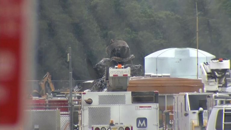 Fire crews are seen dealing with the burned wreckage of the plane