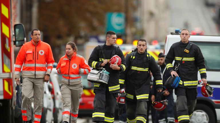 French police and firefighters are seen in front of the headquarters where the officers were killed