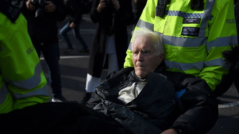 An elderly protester is carried away by police after being arrested