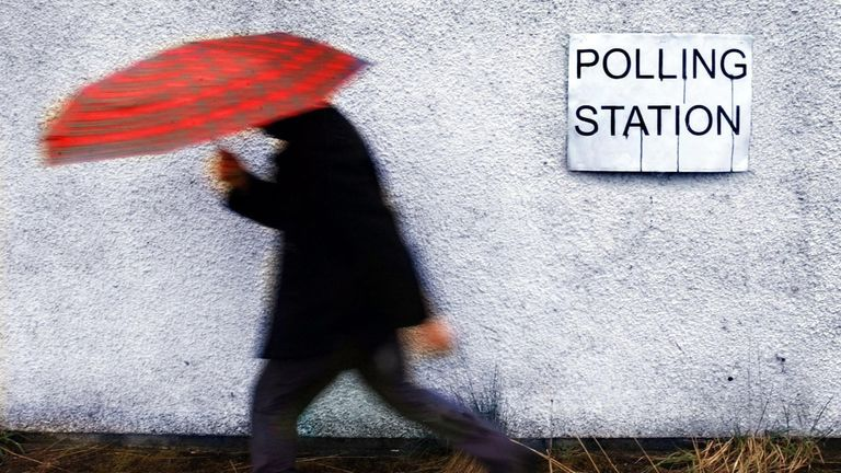 A man makes his way the polling station as heavy rain hits Scotland as voters visited polling stations to vote in the Scottish parliament and local elections.