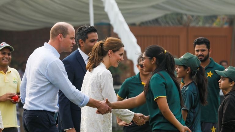 Prince William and Catherine, Duchess of Cambridge, shake hands with children participants of the British Council's DOSTI (friendship) program at the National Cricket Academy in Lahore, Pakistan on Thursday