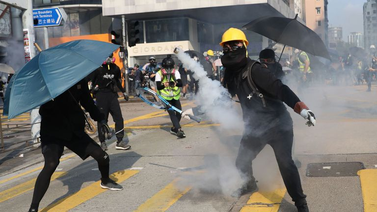 A protester prepares to hit a tear gas canister with a tennis racket in Hong Kong