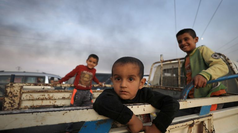 Boys stand at a back of a truck as they flee Ras al Ain