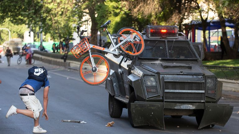 A demonstrator throws a bicycle at a police riot vehicle