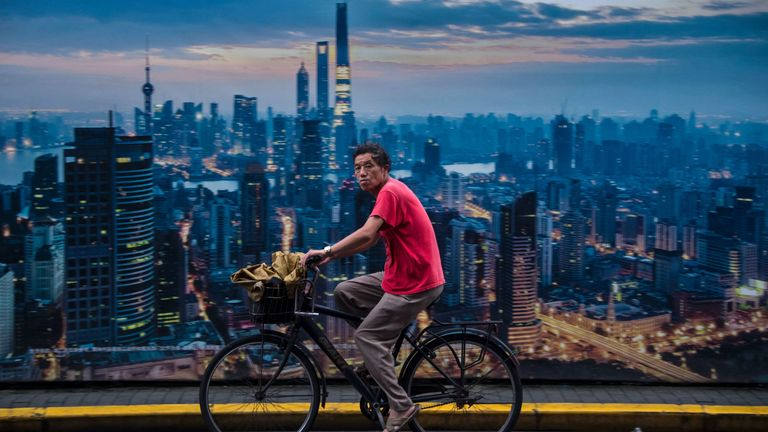 This picture taken on July 11, 2016 shows a man cycling past a billboard showing an aerial view of Shanghai. China's growth slipped to a new seven-year low of 6.6 percent in the second quarter, according to a survey of economists by AFP, despite government efforts to spur activity in the world's second-largest economy