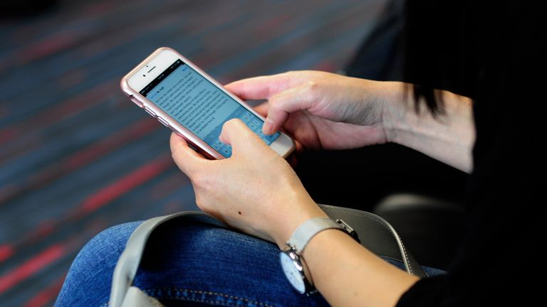 DALLAS, TX - SEPTEMBER 21, 2017: A woman uses her smartphone while waiting to board a plane at the Dallas/Fort Worth International Airport, located roughly halfway between Dallas and Fort Worth, Texas. (Photo by Robert Alexander/Getty Images)