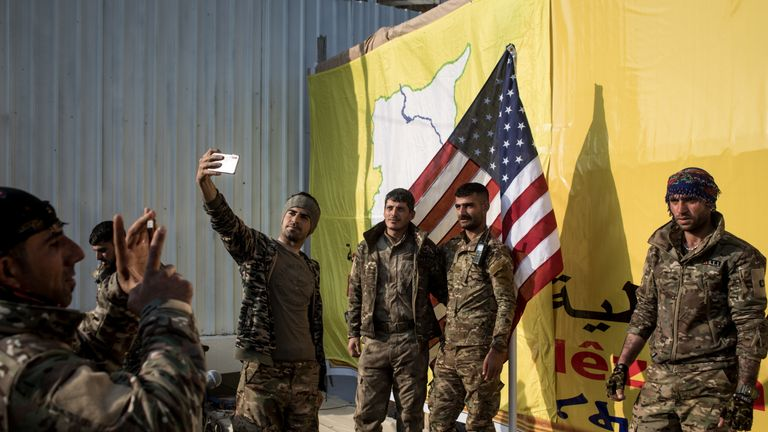 "BAGHOUZ, SYRIA - MARCH 23: Syrian Democratic Forces (SDF) fighters pose for a photo with the American flag on stage after a SDF victory ceremony announcing the defeat of ISIL in Baghouz was held at Omer Oil Field on March 23, 2019 in Baghouz, Syria. The Kurdish-led and American-backed Syrian Defense Forces (SDF) declared on Saturday the ""100% territorial defeat"" of the so-called Islamic State, also known as ISIS or ISIL. The group once controlled vast areas across Syria and Iraq and a population"
