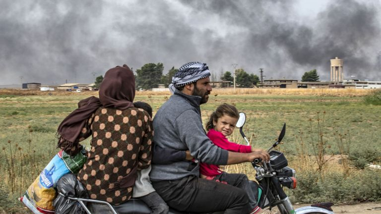 Members of a Syrian family use a motorcycle to flee the countryside of the northeastern Syrian town of Ras al-Ain on the Turkish border, toward the west to the town of Tal Tamr on October 19, 2019. The smoke behind them is from burning tyres used to impede visibility from warplanes. - Turkey's President Recep Tayyip Erdogan fired off a fresh warning today to
