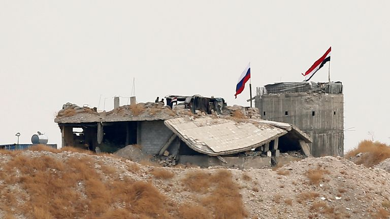 Russian and Syrian national flags are pictured near the northern Syrian village of Zor Magar