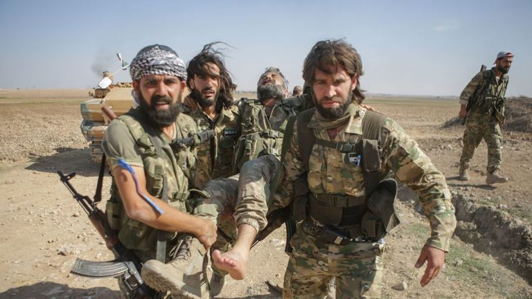 Turkish-backed Syrian rebels carry a wounded fighter as they fought Syrian Kurds in the border town of Tal Abyad