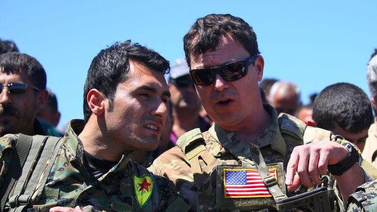 An American officer speaks with a fighter from the Kurdish People's Protection Units near northeastern Syrian town of Derik