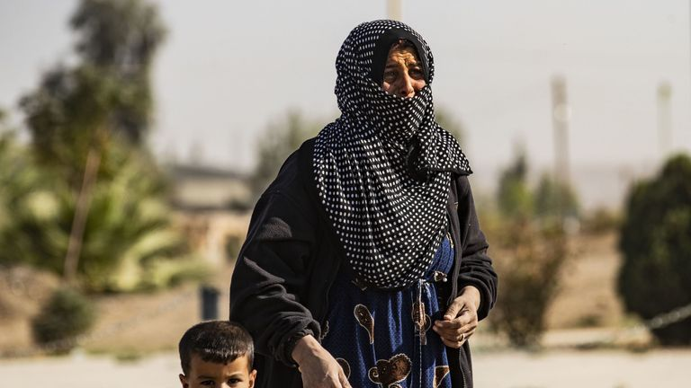 A Syrian woman fleeing the battle zone around the northern flashpoint town of Ras al Ain