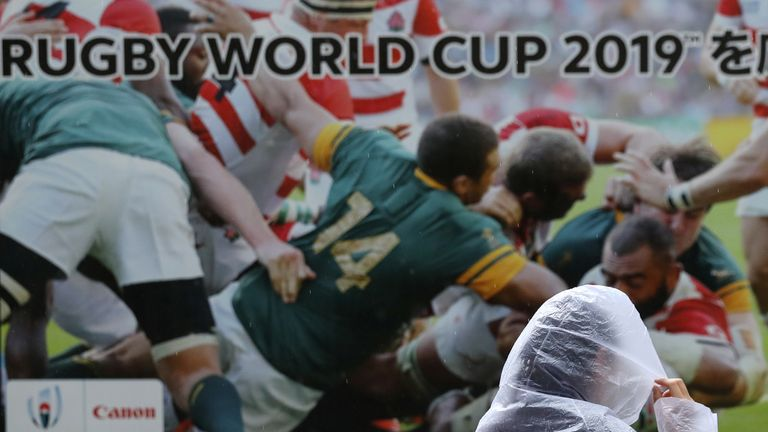 A woman walks past a Rugby World Cup billboard in the Shinagawa