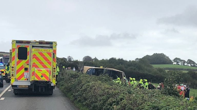 The bus appears to have gone through a hedge and ended up on its side. Pic: DSFRS