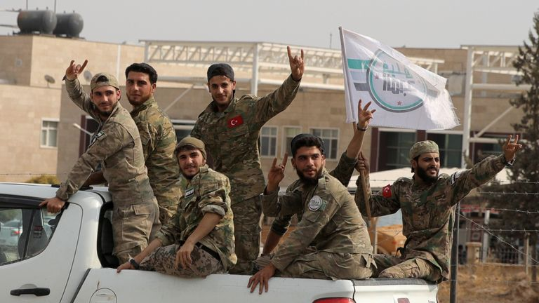 Turkish-backed Syrian rebels ride through the Turkish border town of Akcakale