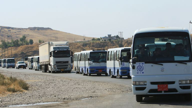 Buses carried Syrian families fleeing violence during the Turkish offensive to displacement camps in Iraq