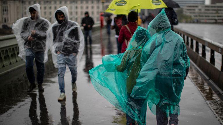 People walk through torrential rain on Westminster Bridge in London