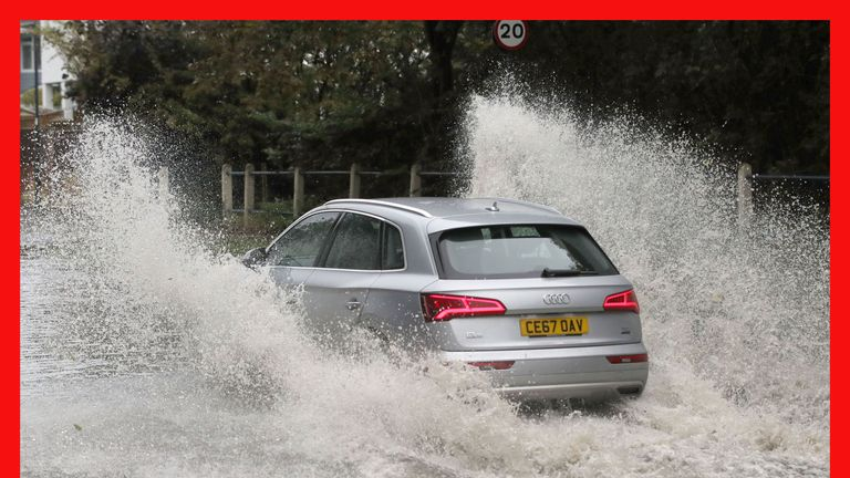 A car drives through a flooded street in Whitley Bay in Northumberland
